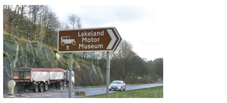A brown sign on the A591 indicating the Lakeland Motor Museum
