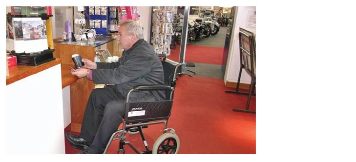 A wheelchair user being welcomed into the museum