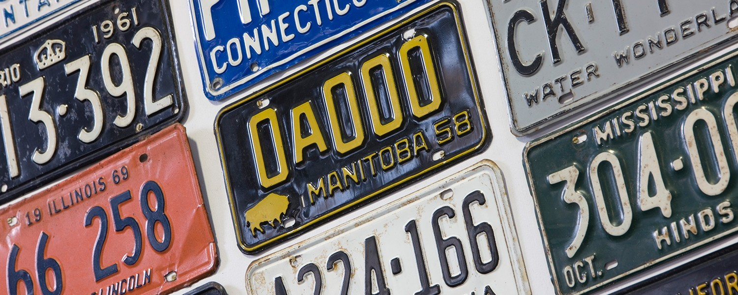 An image of classic licence plates from around the world on a wall of the museum.